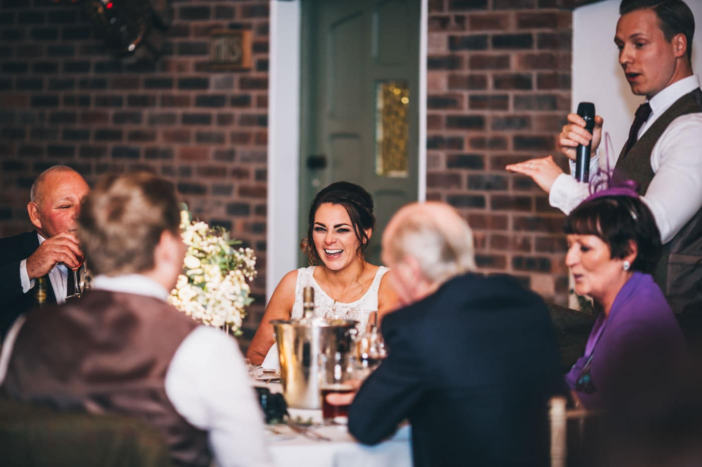 bride laughs during speeches at Owen House wedding barn