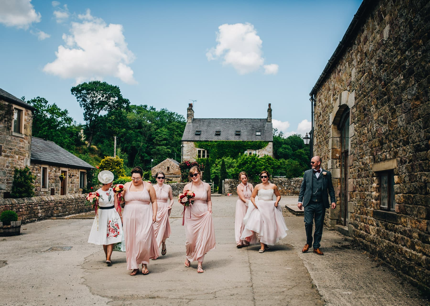 The bride and bridesmaids making their way to the wedding venue, summer wedding, creative wedding photography.